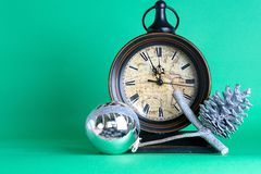 New Year`s clock midnight, bauble and cone on pine fir tree branch. Green background. Christmas greeting card. royalty free stock photography