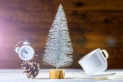 New Year's composition: a clock and a Christmas tree on a wooden background. Christmas background with copy space royalty free stock image