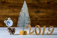 New Year's composition: a clock and a Christmas tree on a wooden background. Christmas background with copy space stock image