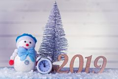 New Year's composition: clock, snowman, inscription 2019 and Christmas tree on a wooden background. Christmas background with copy space royalty free stock photo