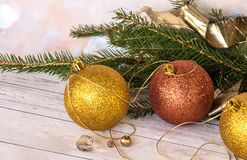 New Year card. Golden balls and new garland with Christmas tree branches. New Year`s composition, a golden thread, balls and a new garland with branches of a stock photo