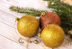 New Year card. Golden balls and new garland with Christmas tree branches. New Year`s composition, a golden thread, balls and a new garland with branches of a royalty free stock images