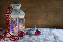 Christmas lantern and balls near a wooden wall. New Year`s composition. A lantern with a garland and balls in the snow Stock Images