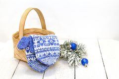 Mittens in a basket and Christmas balls Stock Images