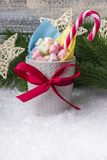 New Year`s composition. A mug with marshmallows of different colors, on the snow with Christmas toys. With a place for your text royalty free stock photography