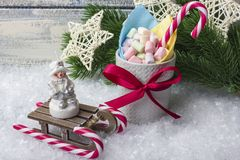 New Year`s composition. A mug with marshmallows of different colors, on the snow with Christmas toys. With a place for your text stock images