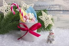 New Year`s composition. A mug with marshmallows of different colors, on the snow with Christmas toys. With a place for your text stock photo