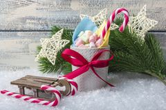 New Year`s composition. A mug with marshmallows of different colors, on the snow with Christmas toys. With a place for your text royalty free stock image