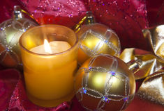 New Year's composition on a red background - ball and ribbon and a candle Royalty Free Stock Photo