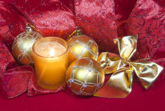 New Year's composition on a red background - ball and ribbon and a candle Royalty Free Stock Images