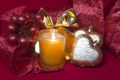 New Year's composition on a red background - ball and ribbon and a candle Stock Photography