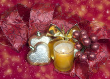 New Year's composition on a red background - ball and ribbon and a candle Stock Images