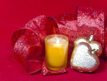 New Year's composition on a red background - ball and ribbon and a candle.  Royalty Free Stock Photos