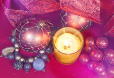 New Year`s composition on a red background - ball and ribbon and a candle Stock Photos
