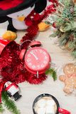 New Year`s composition at the table with the decor, mug and a red clock royalty free stock photo