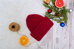 New Year`s Concept. Burgundy winter hat, an orange Christmas tree decorations Stock Photos