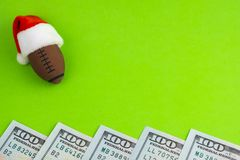 Souvenir ball for American football or rugby in a red Santa Claus hat. Copy space next to dollars on a green background. New Year. New Year`s concept and stock photography