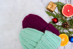 New Year`s Concept. Two knitted hats, citrus fruits and Christmas tree decorations Royalty Free Stock Photos