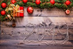 New Year`s decor and festive toys on a wooden table with a red string box with a gift Santa Claus.New Year 2019 lined festoons stock photography