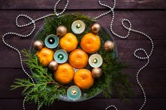 New Year`s decor for the home. Decoration for the Christmas dinner. New Year`s mood. Tangerines, candles and fir branches in the. Decor. Selective focus stock photos