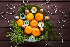 New Year`s decor for the home. Decoration for the Christmas dinner. New Year`s mood. Tangerines, candles and fir branches in the. Decor. Selective focus royalty free stock image