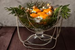 New Year`s decor for the home. Decoration for the Christmas dinner. New Year`s mood. Tangerines, candles and fir branches in the. Decor. Selective focus stock photography