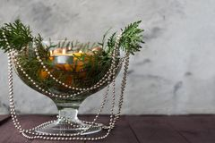 New Year`s decor for the home. Decoration for the Christmas dinner. New Year`s mood. Tangerines, candles and fir branches in the. Decor. Selective focus stock images