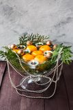 New Year`s decor for the home. Decoration for the Christmas dinner. New Year`s mood. Tangerines, candles and fir branches in the. Decor. Selective focus stock image