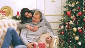 Young couple in love in new year decor with gifts and christmas tree, there is noise in the video. New Year`s decor in the room with a Christmas tree, a stock video