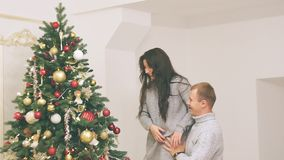 Young couple in love in new year decor with gifts and christmas tree, there is noise in the video. New Year`s decor in the room with a Christmas tree, a stock video footage