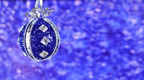 New Year`s decor toy ball. On a Christmas tree in blue on a bright shiny background Stock Photo