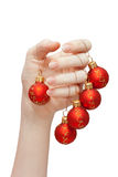 New Year's decoration 3. Red new year balls hanging on fingers, isolated Royalty Free Stock Photography