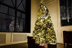 New Year`s decoration room with a huge loft window. Beautiful magic stylish Christmas tree. Gifts in boxes. Amazing bird on a tree. Reflection of yellow cozy Stock Photos