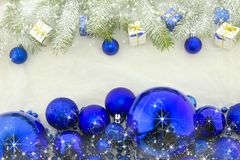 New Year`s decorations, bright blue and white. Christmas decoration with shiny blue balls, packets and green branches of Christmas tree on a white background Stock Image
