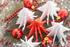 New Year`s decorations, bright red and white. Christmas origami trees on a wooden surface with red beads and red shiny balls Royalty Free Stock Photos