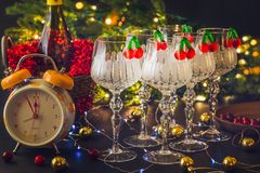 New Year`s decorations with wineglasses, Christmas tree and clock stock image