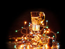 New year's eve. A glass of sparkling wine with some decorations and lights all around it to light it up in the dark Royalty Free Stock Photo