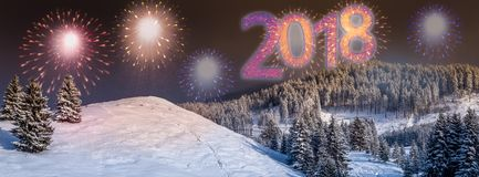 2018 New Year`s eve background with colorful, party fireworks. And 2018 text written on the sky, outdoors, in a winter landscape with snow and fir trees, at Royalty Free Stock Photo