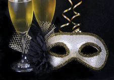 New Year`s Eve carnival mask and champagne. New Year``s Eve themed image of gold and silver carnival mask decorated with black flower and feathers with gold stock image