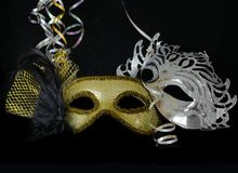 New Year`s Eve carnival masks. New Year`s Eve themed image of gold and silver carnival masks decorated with black flower and feathers with gold ribbons on black royalty free stock photos