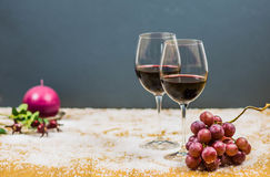New year's eve cheers with two glasses of red wine and grapes. On snow with a candle and butcher's broom on the background Stock Photo