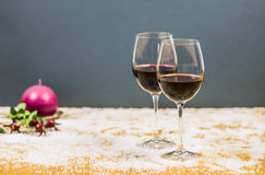 New year's eve cheers with two glasses of red wine and grapes. New year's eve cheers with two glasses of red wine on snow with a candle and butcher's broom on Royalty Free Stock Photography