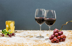 New year's eve cheers with two glasses of red wine and grapes. On snow with a golden candle and butcher's broom on the background Royalty Free Stock Photos