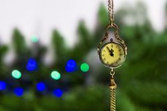 New Year`s Eve, the clock - the medallion shows 23.55. Soon a new time. on the background of a green Christmas tree stock photo
