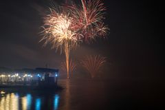New Year`s Eve Fireworks launched from the water with reflections Royalty Free Stock Photo