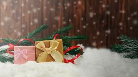 New Year`s Eve gifts box packing with bow of gold and pink. On white snow with red serpentine near Christmas tree Stock Image