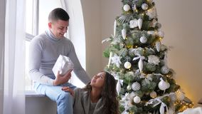 New Year`s Eve, girl sit beside husband with box near window in living room on background decorated xmas tree. New Year`s Eve, girl with artificial snow on hair stock video footage