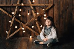 Little pretty girl sits on the background of the New Year`s star. Royalty Free Stock Photos
