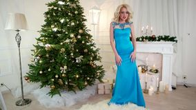New Year's Eve, party, pretty girl in festive dress is dancing near the Christmas tree on Christmas holiday, happy stock footage