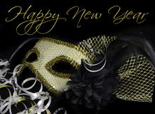 New Year`s Eve carnival mask. New Year`s Eve themed image of gold and silver carnival mask decorated with black flower and feathers with gold and silver ribbons royalty free stock photo